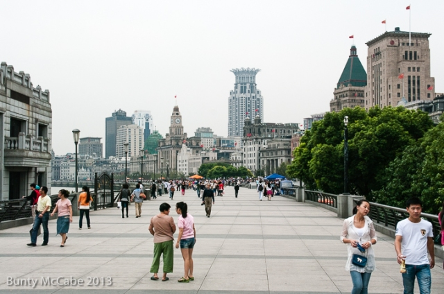 The top of the embankment is a wide walking avenue filled with vendors, tourists and offering a view of the Bund in the distance.