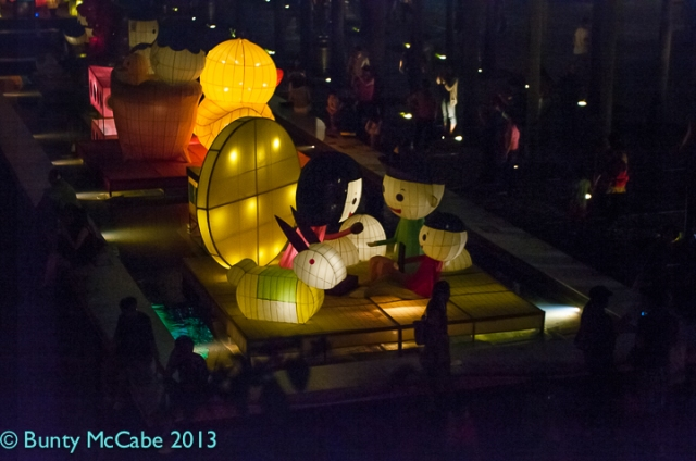 Large lighted sculpture of cartoon characters. You can see how big they are by the size of the people walking around the edges  of the platform.